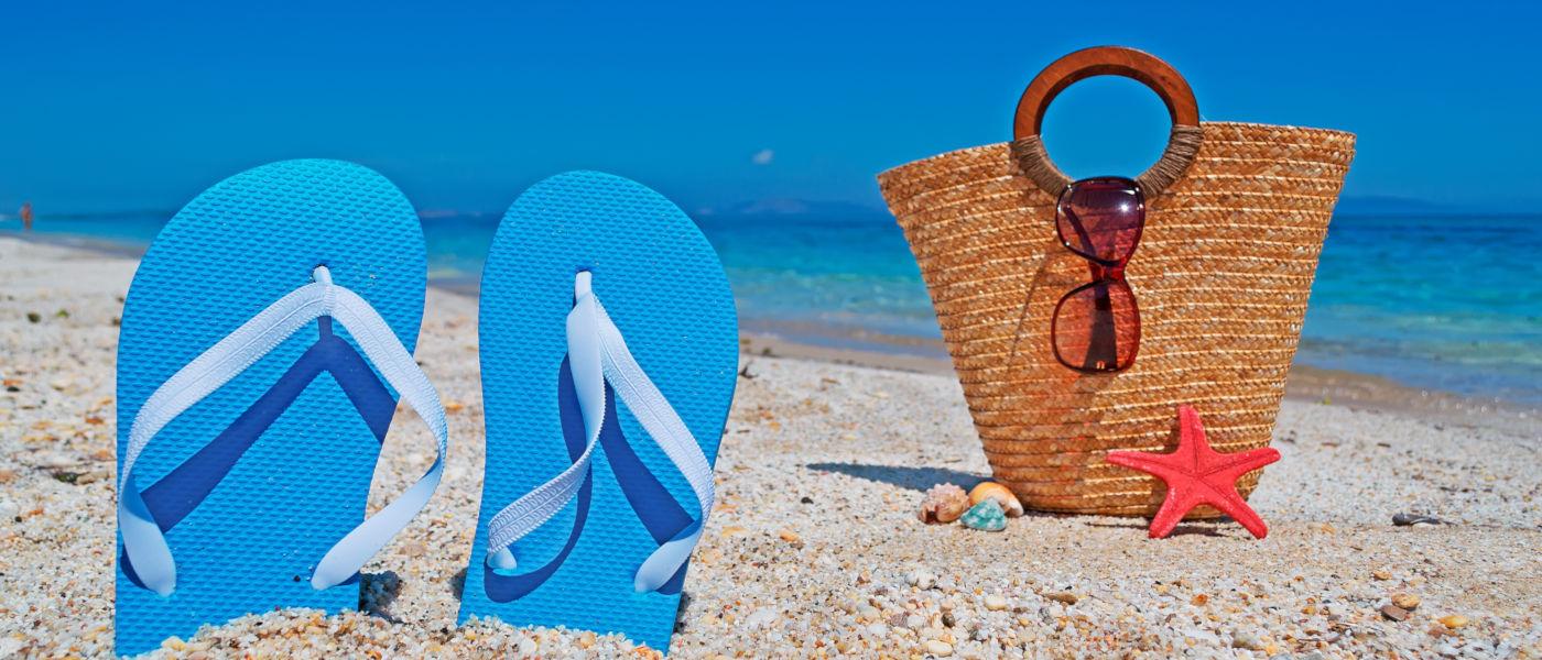 infradito e borsa sulla spiaggia